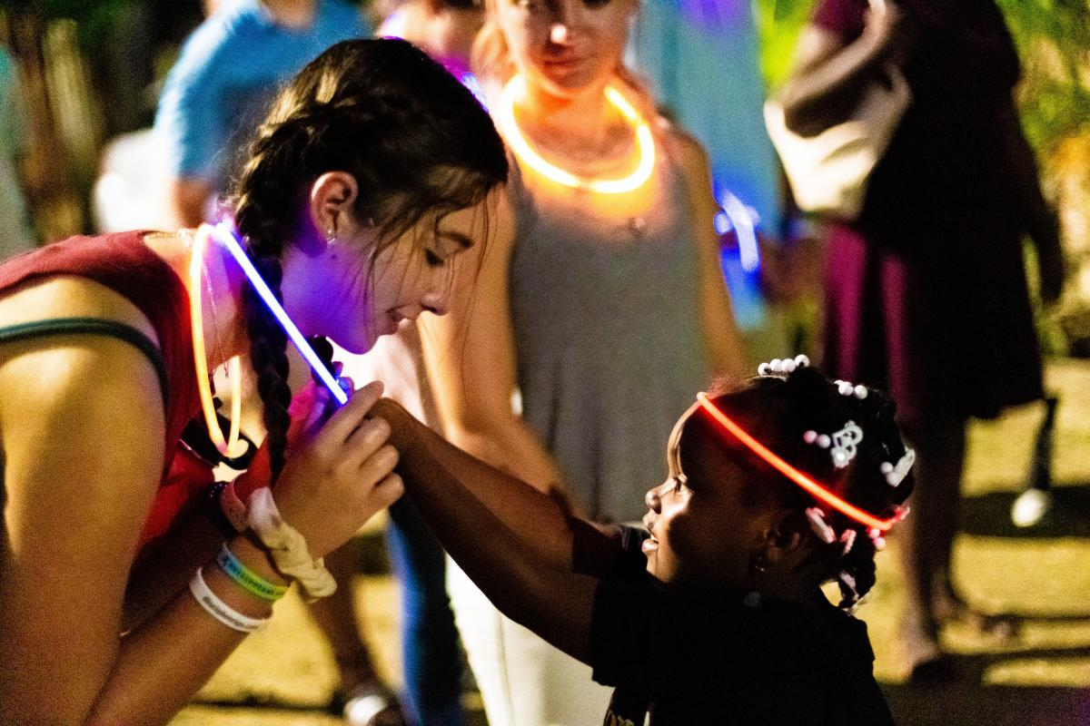 handing out glow sticks during street preaching at night.