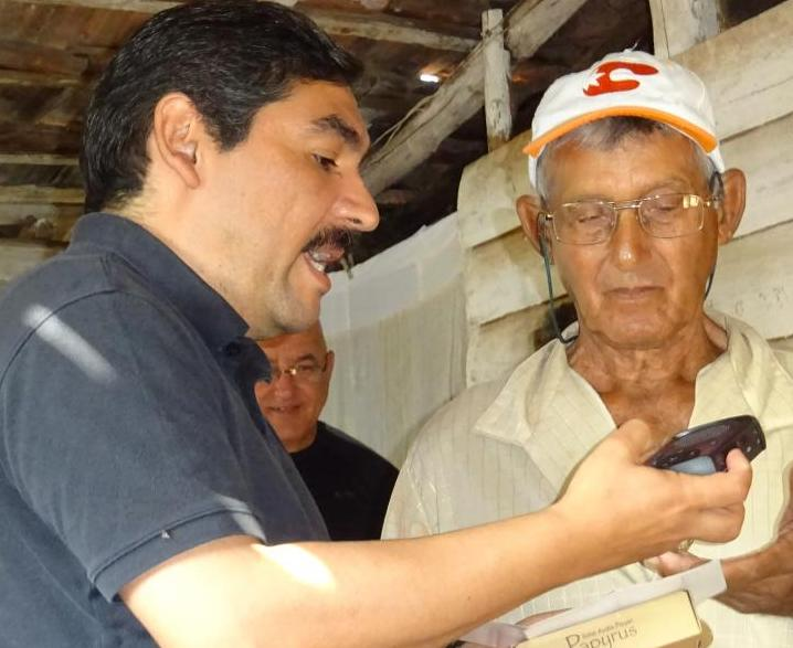 Arthur Puente showing a Cuban preacher how to use the solar player