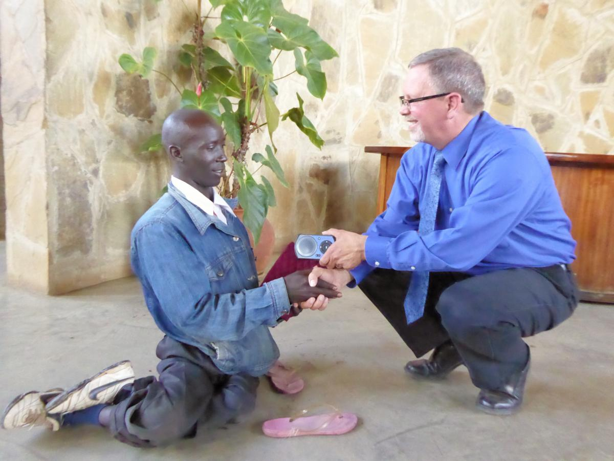 Tim Presenting a Solar Player to Isaac in Kenya